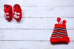 Draufsicht des netten roten Babyschuhs und der roten Schneekappe des Babys auf weißem hölzernem Hintergrund mit Kopienraum stockbilder