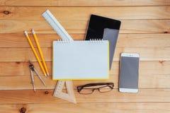 Draufsicht des Notizbuches, des Briefpapiers, der Ziehwerkzeuge und einiger Gläser improvise Stockbild