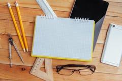 Draufsicht des Notizbuches, des Briefpapiers, der Ziehwerkzeuge und einiger Gläser improvise Lizenzfreies Stockfoto