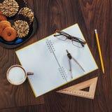 Draufsicht des Notizbuches, des Briefpapiers, der Ziehwerkzeuge und des Kaffees einiger Schalen Stockfoto