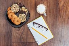 Draufsicht des Notizbuches, des Briefpapiers, der Ziehwerkzeuge und des Kaffees einiger Schalen Lizenzfreie Stockfotografie