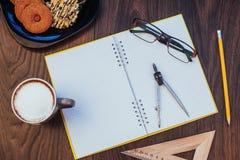 Draufsicht des Notizbuches, des Briefpapiers, der Ziehwerkzeuge und des Kaffees einiger Schalen Stockbild