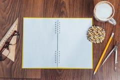 Draufsicht des Notizbuches, des Briefpapiers, der Ziehwerkzeuge und des Kaffees einiger Schalen Lizenzfreie Stockfotos