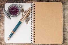 Draufsicht des Notizbuches mit Stift- und Taschenuhr Stockbild