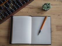 Draufsicht des offenen Buches mit Stift, Abakus und Kaktus im Topf auf woode Stockbild