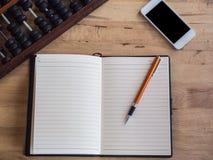 Draufsicht des offenen Buches mit Stift, Abakus und Telefon auf hölzernem Schreibtisch Stockbild