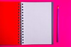 Draufsicht des offenen gewundenen leeren Notizbuches mit Bleistift auf rotem Schreibtischhintergrund stockbild