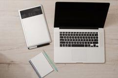 Draufsicht des offenen Laptops, der Grafiktablette und des Notizbuches auf einem Holztisch Lizenzfreies Stockbild