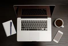 Draufsicht des offenen Laptops, des Notizbuches mit Stift, des intelligenten Telefons und des Bechers Kaffees auf einem schwarzen Lizenzfreie Stockfotos