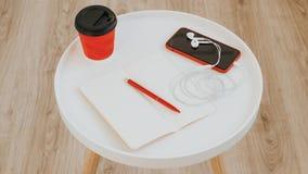 Draufsicht des offenen leeren leeren Briefpapiers mit rotem Stift, Tasse Kaffee, Telefon und Kopfhörern auf weißer hölzerner Tabe stockfoto