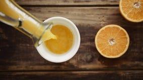 Draufsicht des Orangensaftes gießend in keramische Schale stock footage