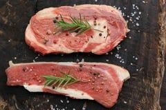 Draufsicht des rohen Rindfleischsteaks mit Rosmarin auf hölzernem dunklem backgrou lizenzfreies stockbild
