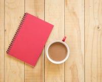 Draufsicht des roten Buches und der Kaffeetasse auf Holztisch Stockfotos