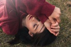Draufsicht des schönen jungen kaukasischen Frauenlächelns und der geschlossenen Augen, tragender Strickpullover, liegend auf dem  stockbilder