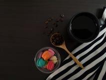 Draufsicht des schwarzen Kaffees mit Morgennachtischen auf dem schwarzen Speisetische lizenzfreies stockfoto
