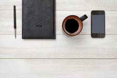 Draufsicht des schwarzen Notizbuches und des Stiftes mit heißem Kaffee der Schale Lizenzfreie Stockfotografie