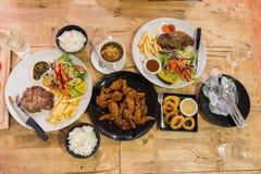 Draufsicht des SchweinefleischPfeffersteaks mit Gemüse und Pommes-Frites und Soße und Huhnwingin und gebratene Zwiebelweißplatte Stockbild