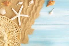 Draufsicht des Seestrohhutes und der Seeoberteile auf dem Meersand auf einem blauen hölzernen Hintergrund, Sommerkonzept auf leer lizenzfreies stockfoto