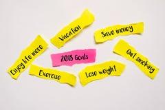 Draufsicht des Stückes des Blattes von rosa und gelbem Papier mit Wörtern 2018 Ziele, sparen Geld, beendigtes Rauchen, verlieren  stockfoto