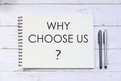 Draufsicht des Stiftes und des Notizbuches geschrieben mit Frage, warum uns wählen Sie? auf weißem hölzernem Hintergrund stockbild