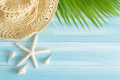 Draufsicht des Strohhutes, der Bl?tter und der Oberteile auf dem blauen h?lzernen Hintergrund, Sommerkonzept auf leerem Purplehea stockfoto