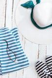 Draufsicht des Strohhutes, der gestreiften Kleidung und der Turnschuhe auf weißer hölzerner Tischplatte Stockfotos