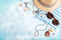 Draufsicht des Strohhutes, der Sonnenbrille und der gestreiften Kleidung auf blauer Tischplatte mit weißem Sand Stockfoto