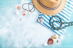 Draufsicht des Strohhutes und der gestreiften Kleidung auf blauer Tischplatte mit weißem Sand Lizenzfreies Stockbild