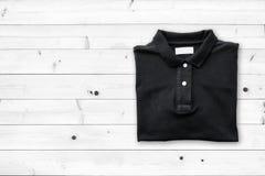 Draufsicht des T-Shirts auf altem Holzfußbodenhintergrund Stockbild