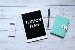 Draufsicht des Taschenrechner-, Notizbuch-, Stift- und Tabletten-PC geschrieben mit ' PENSION PLAN' auf hölzernem Hinte lizenzfreie stockfotografie