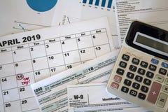 Draufsicht des Taschenrechners, der Steuerformulare, der Diagramme und des Kalenderblattes mit Steuerdatum markierte lizenzfreie stockfotografie