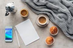 Draufsicht des Tasse Kaffees mit Muffins leeres Papier und Smartphone mit Anmeldung App auf Schirm auf Betondecke mit gestrickt lizenzfreie stockfotografie