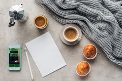 Draufsicht des Tasse Kaffees mit süßen Muffins leeres Papier und Smartphone mit Anmeldung App auf Schirm auf Betondecke mit stockfotografie