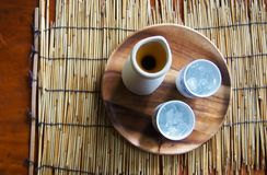 Draufsicht des Teetopfes und des Glases Eistees Auf einer hölzernen Platte die auf eine Bambusmatte und auf eine Tabelle gesetzt  stockfoto