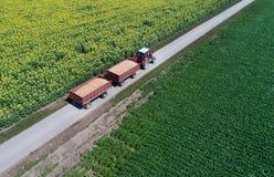 Draufsicht des Traktors mit Anhängern auf Landstraße Stockfotos