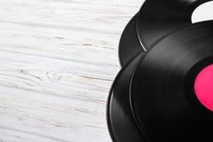Draufsicht des Vinylaufzeichnungsstapels über hellem Holztisch mit Kopienraum für Text Stockfotografie
