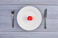 Draufsicht des weißen Tellers mit Tomate Lizenzfreie Stockfotos