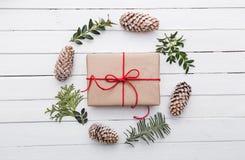 Draufsicht des Weihnachtsgeschenks eingewickelt im Handwerk und mit verschiedenen natürlichen Sachen auf weißem Holz verziert Lizenzfreies Stockbild