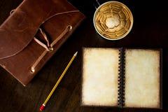 Draufsicht des Weinlesepapierbuches mit Tasse Kaffee auf hölzerner Rückseite Lizenzfreies Stockbild