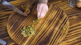 Draufsicht, die grüne Oliven für griechischen Salat auf Holztisch schneidet Schneidene Prozeßoliven für vegetarische Küche stock video