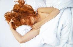 Draufsicht einer attraktiven, jungen, rothaarigen Frau, Haar wild, schlafend, im Gesicht, genießt neue weiche Bettwäsche und matt stockbilder