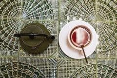 Draufsicht einer grünen Teekanne und der Tasse Tee Stockfoto
