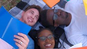 Draufsicht einer Gruppe Vorschulstudenten, die auf dem Gras liegen und ein Klassenfreien nehmen stock video