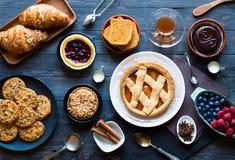 Draufsicht einer hölzernen Tabelle voll der Kuchen, Früchte, Kaffee, Kekse stockbild