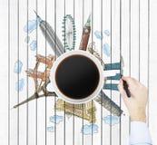 Draufsicht einer Kaffeetasse und der Hand zeichnet bunte Skizzen der berühmtesten Städte in der Welt Das Konzept des Reisens Stockbild