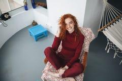Draufsicht einer lächelnden glücklichen Frau, die auf einem Stuhl sitzt Stockfoto