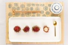 Draufsicht einer Rambutanwüste mit Chinaware, goldenem Löffel und Essstäbchen lizenzfreie stockfotos