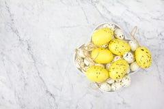 Draufsicht einer weißen Platte mit den gelben und nachgeahmten Fleckwachteleiern auf dem Marmorhintergrund stockfotografie