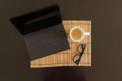 Draufsicht eines Arbeitsplatzes mit Kaffee, Laptop und Sonnenbrille Stockfotos