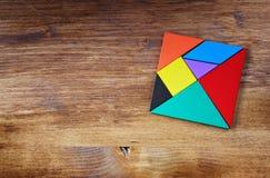Draufsicht eines fehlenden Stückes in einem quadratischen Tangrampuzzlespiel, über Holztisch Lizenzfreies Stockfoto